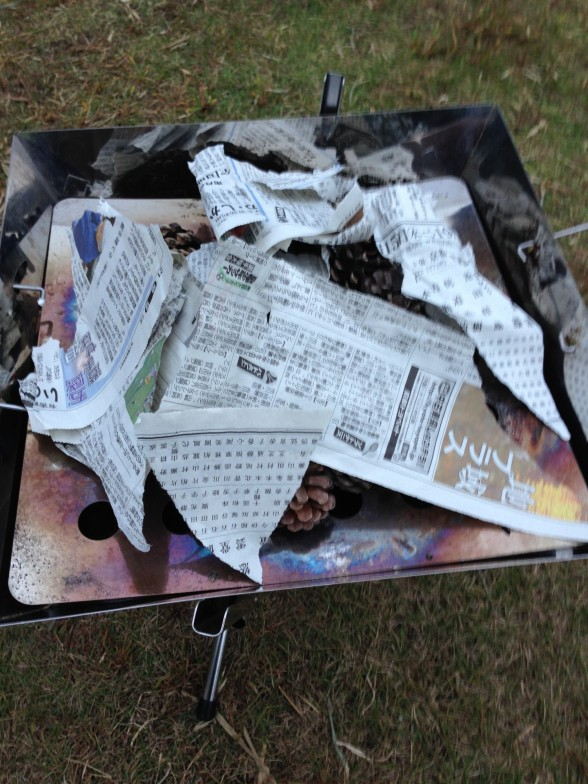 ユニフレーム ファイアグリルに新聞紙と松ぼっくりをセット
